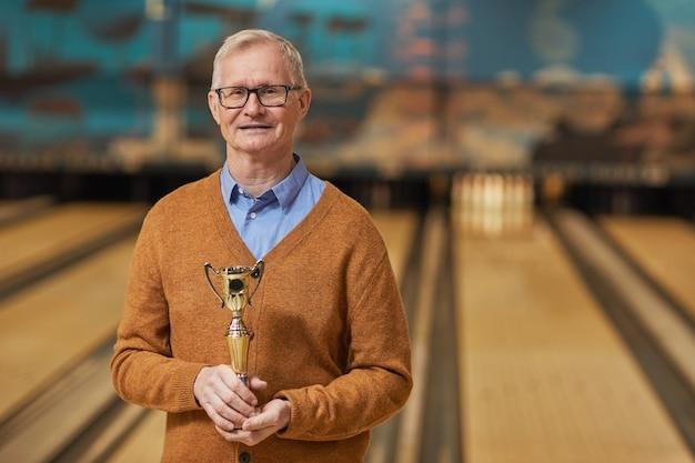 Portrait de taille d'un homme âgé souriant tenant un trophée et regardant la caméra en se tenant debout dans un bowling après avoir remporté le match, espace de copie