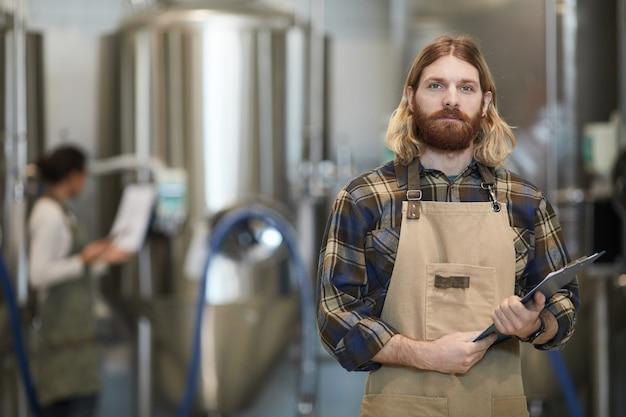 Portrait de taille d'homme barbu portant un tablier posant dans l'atelier d'une brasserie industrielle moderne, espace de copie