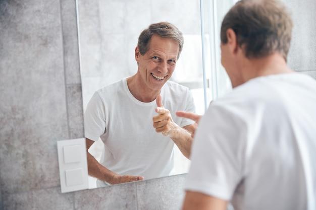 Portrait de taille d'un homme mûr aux cheveux courts plein d'entrain pointant son doigt vers le miroir