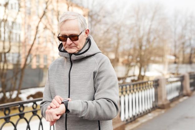 Portrait de taille d'un homme senior moderne vérifiant la montre intelligente tout en courant à l'extérieur en hiver, espace de copie