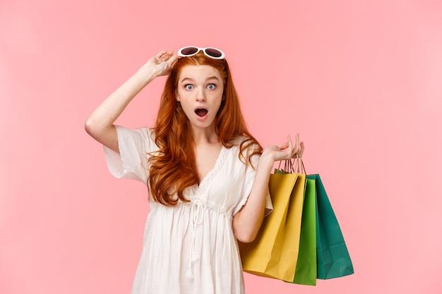 Portrait de taille impressionné, gingembre excité et surpris, cheveux bouclés foxy, lunettes de soleil au décollage, voir des rabais incroyables en magasin, dépêchez-vous d'acheter quelque chose, tenant des sacs avec des articles de magasinage