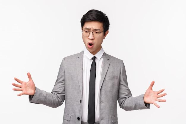 Portrait de taille d'un jeune employé de bureau asiatique impressionné en costume, façonnant quelque chose de grand, décrivez un grand objet avec les mains tendues, bouche ouverte haletant, debout sur un mur blanc