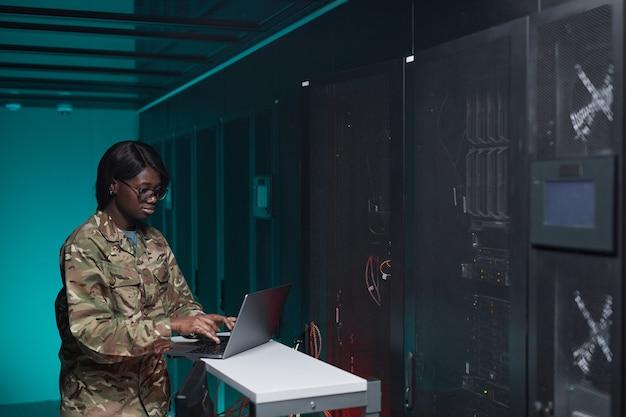 Portrait de taille d'une jeune femme afro-américaine portant un uniforme militaire à l'aide d'un ordinateur lors de la configuration du réseau dans la salle des serveurs, espace de copie