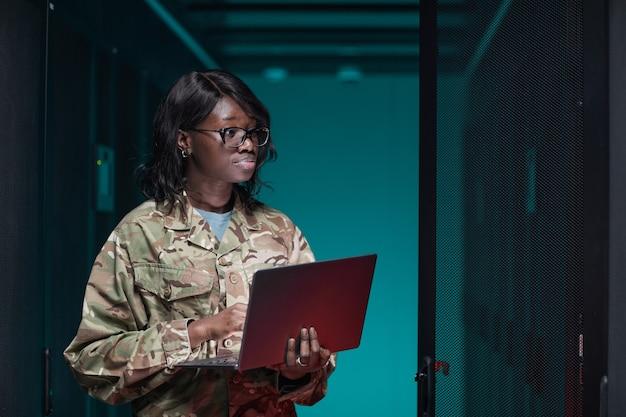 Portrait de taille d'une jeune femme afro-américaine portant un uniforme militaire utilisant un ordinateur portable tout en se tenant dans la salle des serveurs, espace pour copie