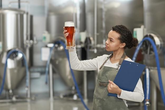 Portrait de taille d'une jeune femme afro-américaine tenant un verre à bière tout en inspectant la qualité de la production à l'usine de brassage, espace de copie