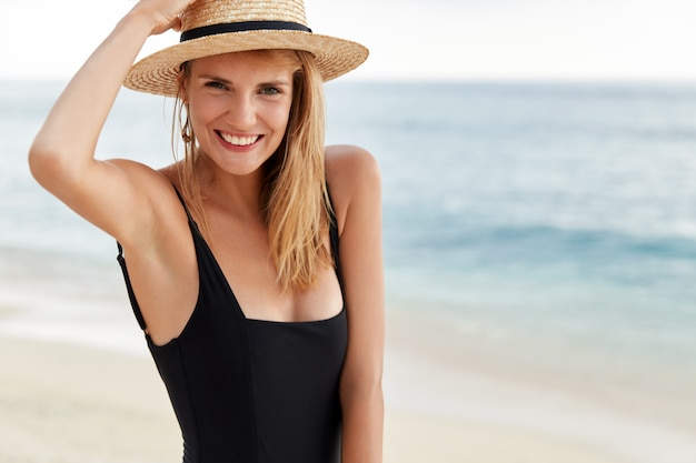 Le portrait à la taille d'une jeune femme mignonne voyageuse en bikini et chapeau découvre un pays tropical, pose sur le littoral de l'océan, heureux de passer des vacances d'été à l'étranger, a une belle expression positive.