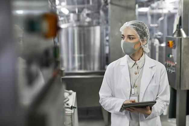 Portrait à la taille d'une jeune femme portant un masque et tenant une tablette numérique lors de l'inspection de contrôle de la qualité à l'usine alimentaire, espace de copie