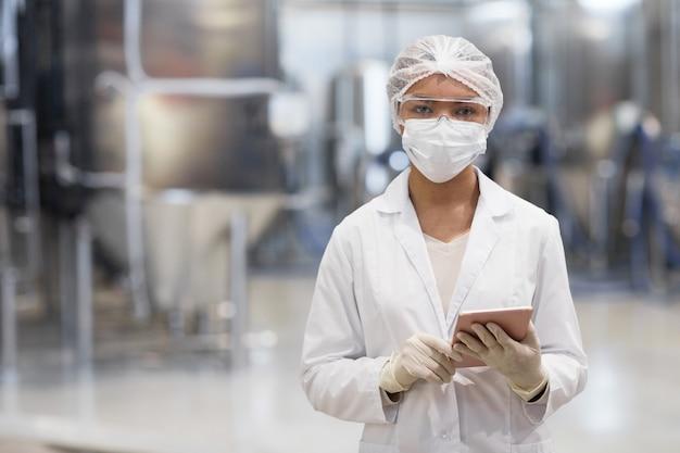 Portrait à la taille d'une jeune femme travaillant dans une usine chimique et regardant la caméra tout en portant des vêtements de protection, espace pour copie