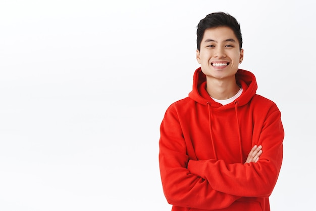 Portrait à la taille d'un jeune homme asiatique confiant et prospère en sweat à capuche rouge, l'air heureux de croiser les mains sur la poitrine satisfait, a réussi le test, optimiste quant à l'obtention de ce travail, debout sur un mur blanc.