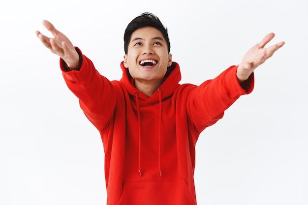 Portrait à la taille d'un jeune homme asiatique rêveur et heureux, vêtu d'un sweat à capuche rouge, levant les mains et le tenant pour attraper quelque chose, souriant heureux, le succès venant dans ses bras, mur blanc.