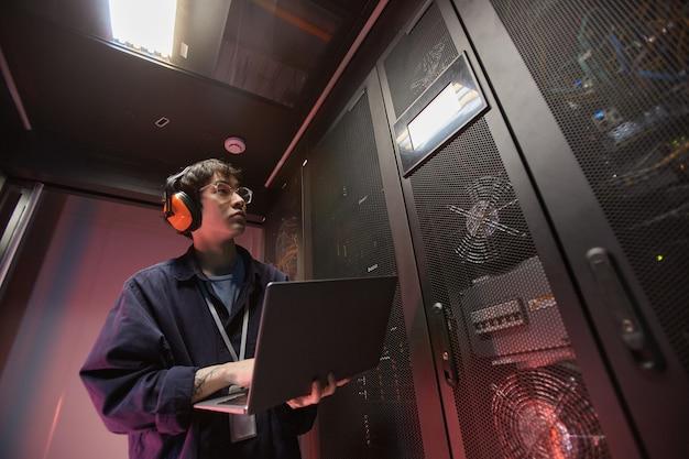 Portrait à la taille d'un jeune homme asiatique utilisant un ordinateur portable lors de la configuration d'un réseau de superordinateurs dans la salle des serveurs, espace de copie