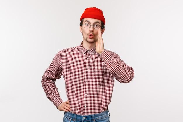 Portrait à la taille d'un jeune homme drôle avec barbe et moustache en bonnet rouge, lunettes, appeler quelqu'un, chercher un ami dans la foule, tenir la main près de la bouche, bavarder, chuchoter secret