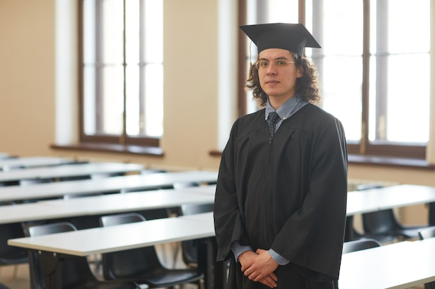 Portrait à la taille d'un jeune homme portant une robe de graduation et regardant la caméra tout en posant dans l'auditorium de l'école, espace pour copie