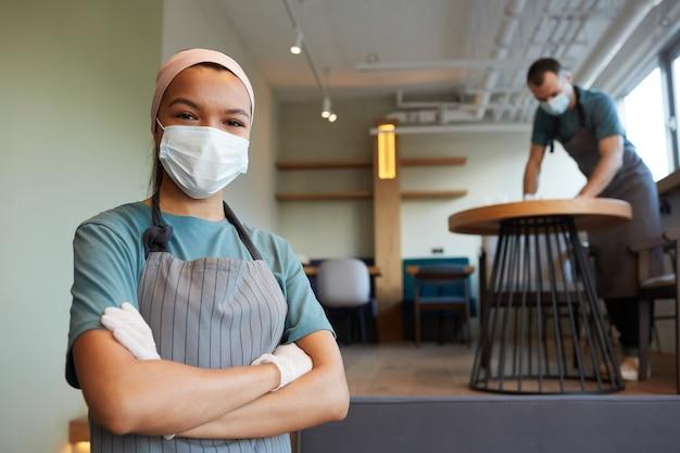 Portrait à la taille d'une jeune serveuse portant un masque et un tablier regardant la caméra en se tenant debout dans un café avec un homme nettoyant les tables en arrière-plan, mesures de sécurité covid, espace de copie