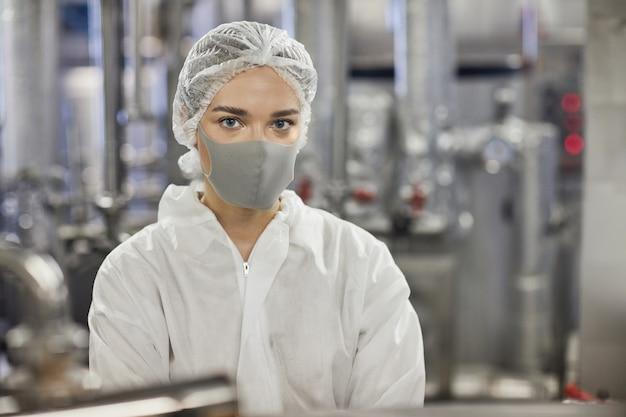 Portrait à la taille d'une jeune travailleuse portant un masque et regardant la caméra tout en travaillant dans une usine alimentaire, espace pour copie