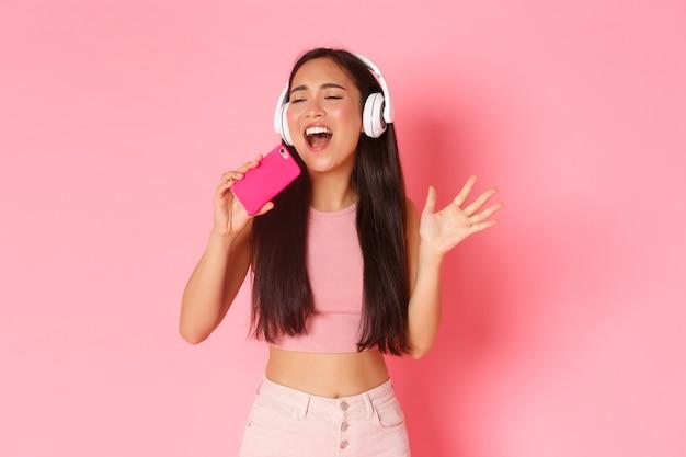 Portrait de taille de jolie fille asiatique élégante fermer les yeux et chanter le long de la chanson