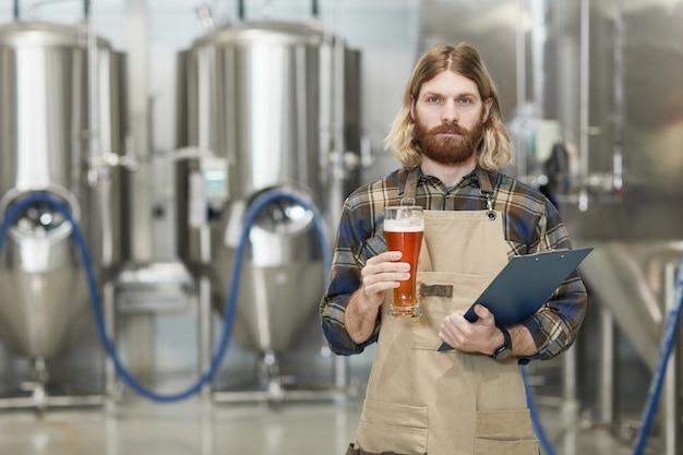 Portrait à la taille d'un maître brasseur barbu tenant un verre à bière et regardant la caméra en se tenant debout dans l'atelier de l'usine de brassage, espace pour copie