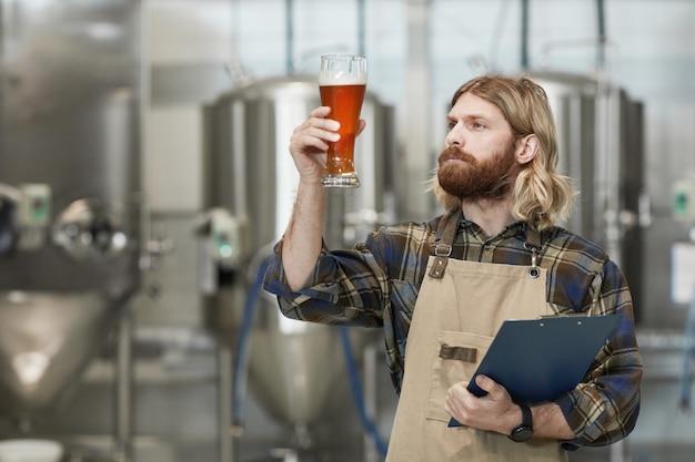 Portrait à la taille d'un maître brasseur barbu tenant un verre à bière tout en inspectant la qualité de la production à l'usine de brassage, espace de copie