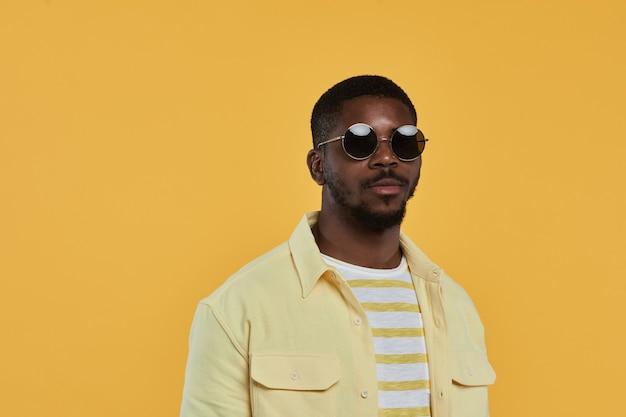 Portrait de taille minimale d'un homme afro-américain à la mode portant des lunettes de soleil et regardant la caméra avec ...