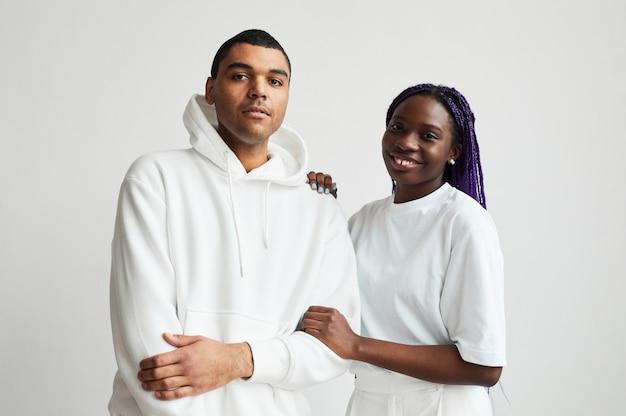 Portrait de taille minimale d'un jeune couple de race mixte vêtu de blanc tout en posant pour la caméra