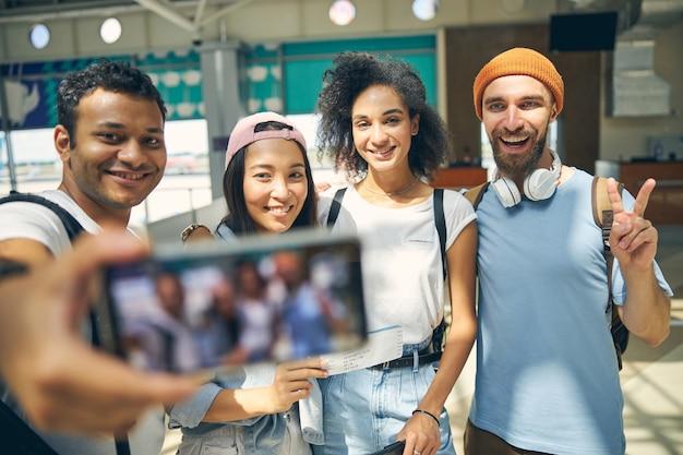 Portrait de taille de personnes élégantes dans des vêtements décontractés souriant et faisant des gestes à l'appareil photo