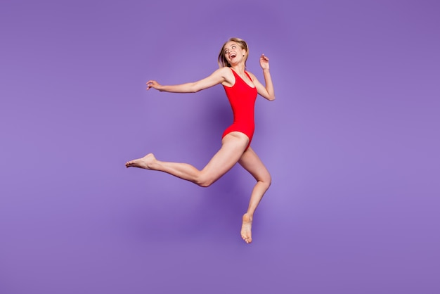 Portrait en taille réelle du modèle de jeune femme sautant sur le violet