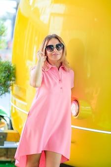 Portrait en taille réelle de la jeune fille blondy dans un stand rose tenant ses mains isolé sur fond jaune vif avec copie espace pour le texte