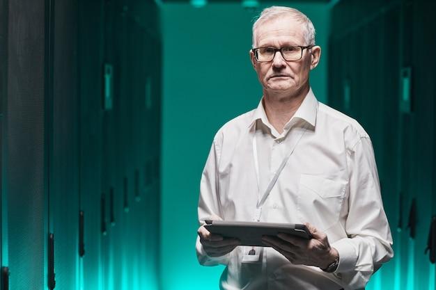 Portrait de taille d'un scientifique de données senior regardant la caméra et tenant une tablette tout en travaillant avec un superordinateur dans une lumière bleue futuriste, espace de copie