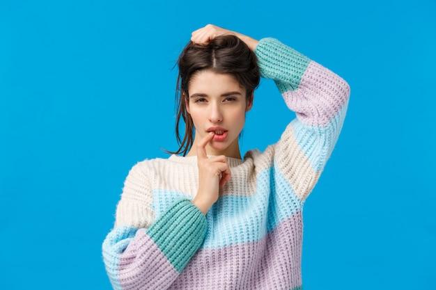 Portrait à la taille sensuelle et féminine, une femme affirmée veut séduire quelqu'un, plisser les yeux avec un regard coquin et coquet, toucher une lèvre séduisante, debout dans une pose sexy sur bleu