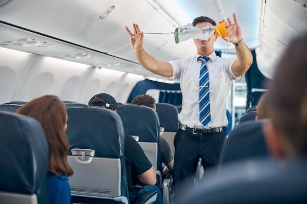 Portrait à la taille d'un steward montrant les règles de sécurité et les instructions d'utilisation des masques à oxygène dans l'avion commercial