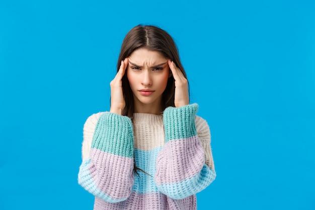 Portrait de taille tendue jeune femme mal à l'aise, toucher les tempes et plisser les yeux, avoir une énorme gueule de bois, des sentiments douloureux dans la tête, des migraines, des maux de tête debout sur le mur bleu