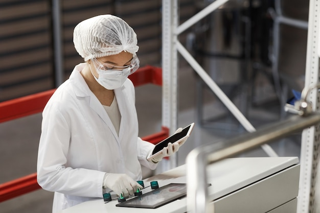 Portrait de taille d'une travailleuse appuyant sur les boutons du panneau de commande tout en faisant fonctionner des unités de machine dans une usine chimique moderne, espace de copie
