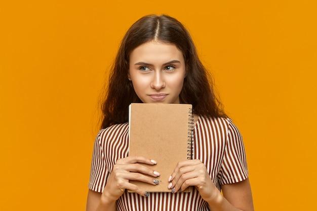 Portrait de talentueuse jeune femme séduisante artiste en robe rayée tenant un nouveau carnet de croquis