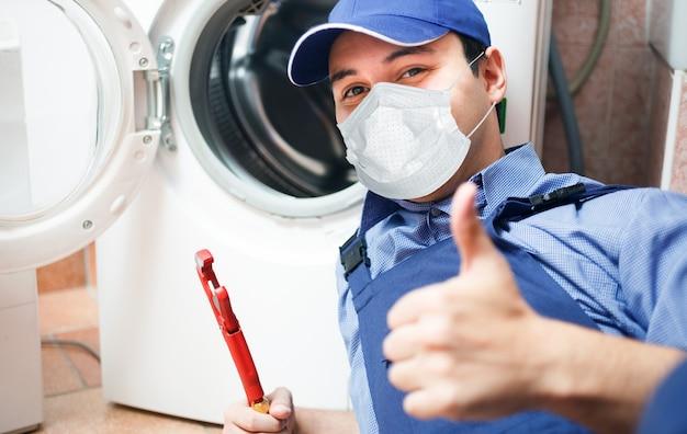 Portrait d'un technicien réparant une machine à laver, un concept de covid ou de coronavirus