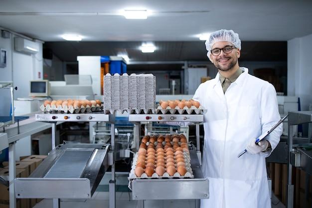 Portrait de technologue d'usine alimentaire avec filet à cheveux et gants hygiéniques debout par transport industriel et machine d'emballage des œufs dans l'usine de transformation des aliments.