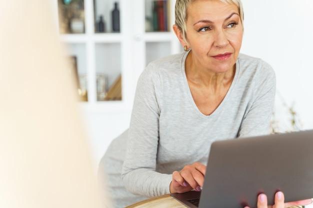 Portrait d'une télétravailleuse senior rêveuse séduisante avec un ordinateur portable regardant au loin