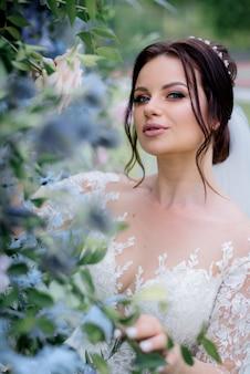Portrait tendre de la belle mariée brune près de feuilles vertes, jour du mariage