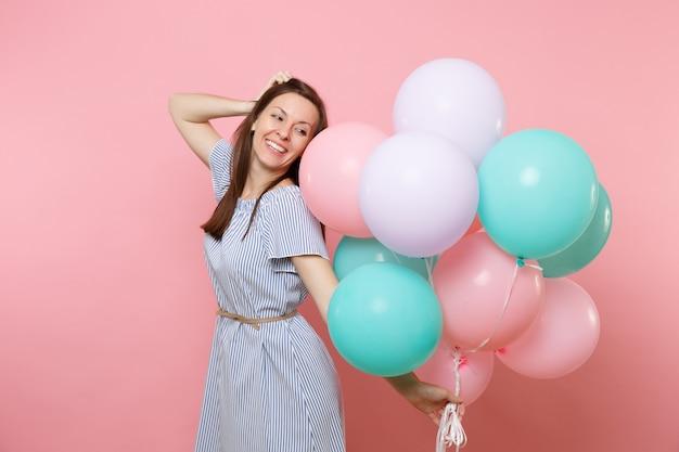 Portrait d'une tendre jeune femme souriante en robe bleue tenant des ballons à air colorés gardant la main près de la tête isolée sur fond rose vif. fête d'anniversaire, concept d'émotions sincères.
