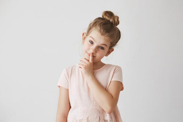 Portrait d'une tendre petite fille aux cheveux blonds en coiffure chignon, tenant le doigt sur les lèvres et souriant, avec une expression de visage calme.