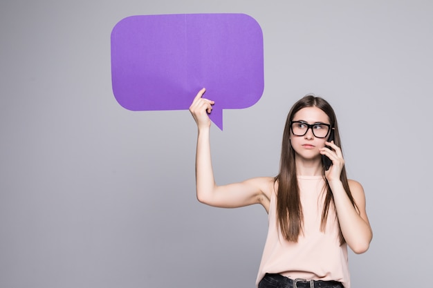 Portrait, de, a, tenue femme, vide, bulle discours, et, conversation téléphone mobile, isolé, sur, mur gris