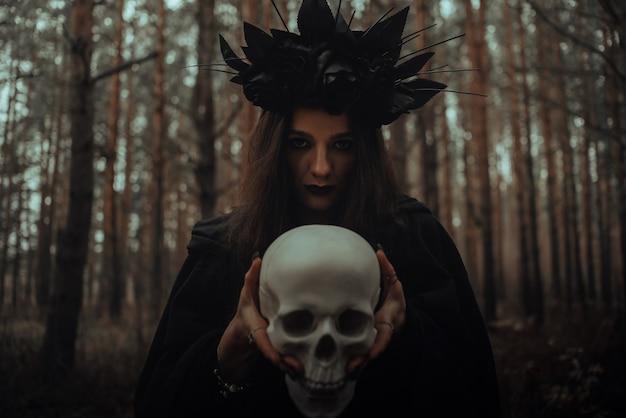 Portrait d'une terrible sorcière avec un crâne dans les mains d'un homme mort effectue un rituel mystique occulte dans la forêt