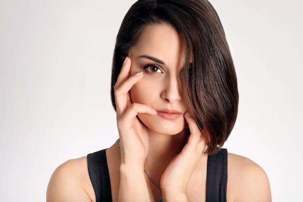 Portrait de tête de beau modèle féminin brune avec les mains près du visage sur fond blanc.