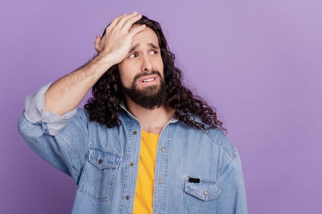 Portrait de tête de main de type triste regarde l'espace vide sur fond violet