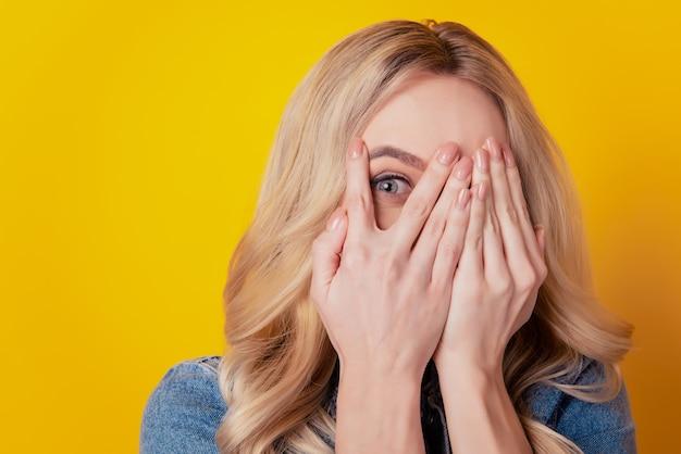 Portrait de timide adorable fille charmante paumes cacher les yeux du visage regarder la caméra sur fond jaune