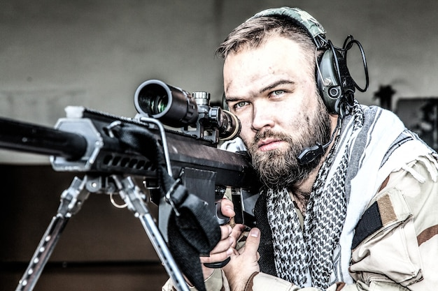 Portrait d'un tireur d'élite de l'us navy seal en position de tir, armé d'un fusil de sniper de gros calibre avec lunette de visée, portant un casque tactique avec microphone, observant le territoire, recherchant des cibles