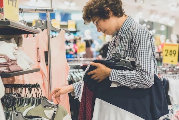Portrait de ton vintage de jeune homme adolescent dans le magasin de vêtements décontractés acheter une nouvelle usure