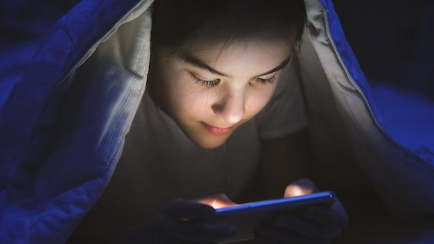Portrait tonique d'une adolescente souriante allongée dans son lit avec un smartphone et naviguant sur internet.