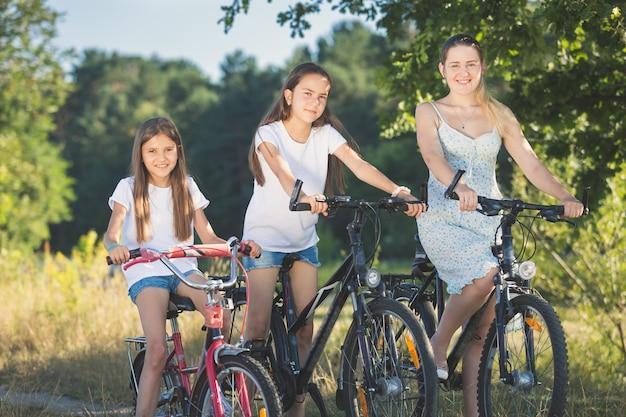 Portrait tonique de deux soeurs à vélo avec mère au pré au bord du lac