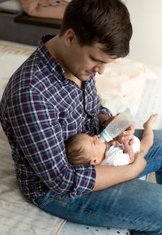 Portrait tonique du jeune père nourrissant son fils nouveau-né avec du lait