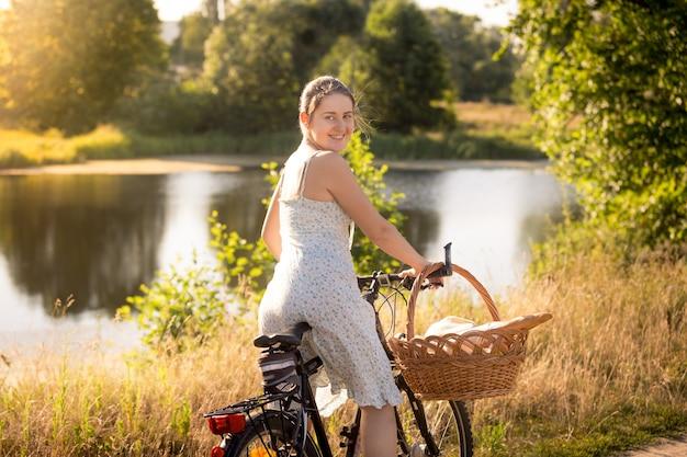 Portrait tonique de jeune femme en robe assise à vélo au bord du lac